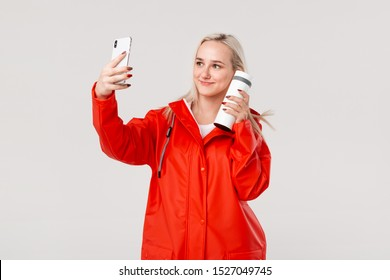 Blond woman in a red raincoat making selfie with smartphone holding white thermal mug with hot beverage isolated over white background.