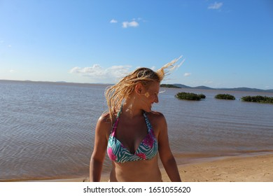 Blond woman shaking her head with wet hair at the beach wearing a blue bikini with blue sky and water in the background