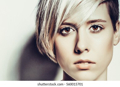 Blond woman with short hair close-up on a light background