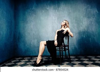 blond woman sit in empty room in elegant black dress and high heels