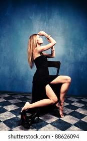 blond woman sit in empty room in elegant black dress barefoot