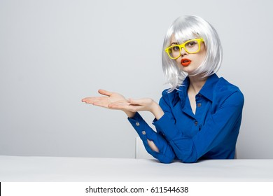 Blond woman sits at the table with glasses teacher