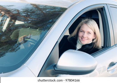 Blond woman sitting behind the wheel of the car and smiling