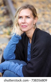 blond woman sitting outside on train tracks and looking pensive