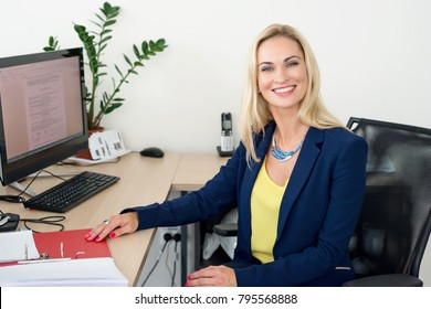 Blond woman is sitting at a table in the office and smiling