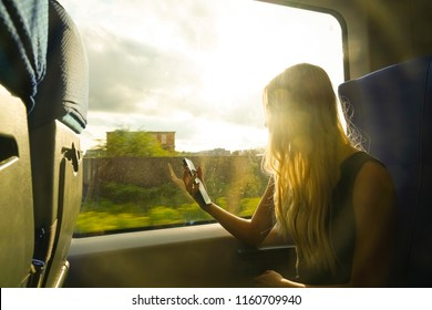 blond Woman sitting at train and looking to mobil phone under sunlight at day time. sunny day