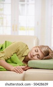 Blond woman sleeping with blanket on couch in sunlit living room at home.