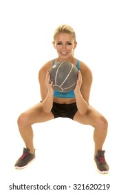 a blond woman with a smile, doing a squat with a medicine ball.