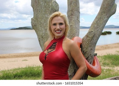 Blond woman smiling at the camera leaning back on a tree with the beach , sand and water and a blue sky with clouds in the background