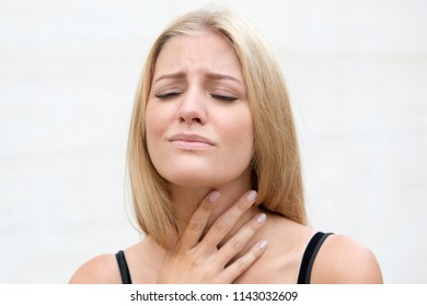 blond woman with sore throat in summer