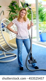 blond woman standing in living room with hoover