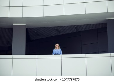 Blond woman is standing on a balcony in a modern building