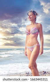 blond woman standing on the beach in bikini and with swimming goggles