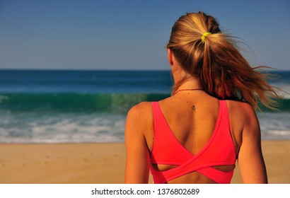 Blond woman standing at sea on summer