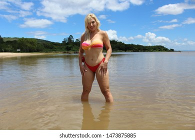 Blond woman standing in the water wearing a bikini with blue coudly sky in the background