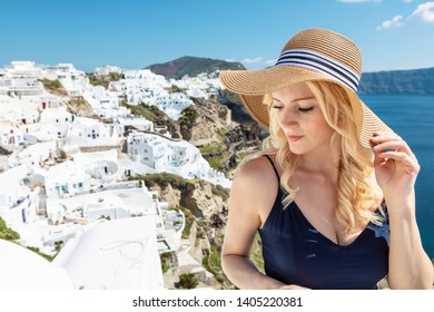blond woman with a sun hat and a navy blue jumpsuit in Oia on Santorini