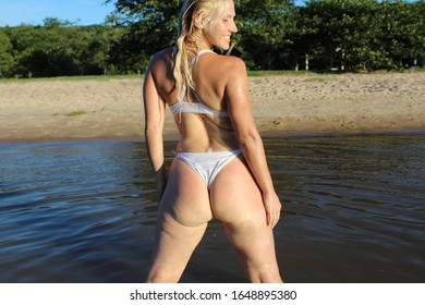 Blond woman in the sun looking to the side in the beach with water and beach sand in the background smiling