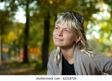 Blond woman with sunglasses portrait in a autumn park.