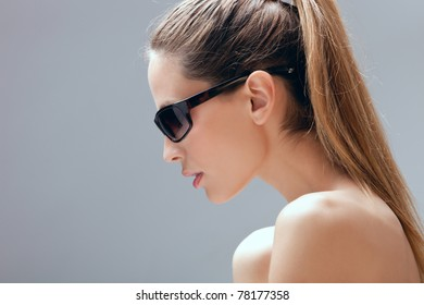 blond woman with sunglasses portrait, profile,  studio shot