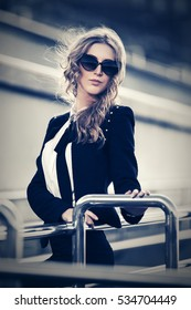 Blond woman in sunglasses walking on city street Stylish fashion model outdoor