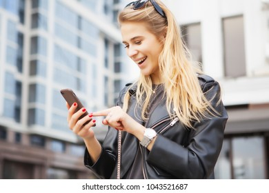 blond Woman using a smart phone in the street in spring