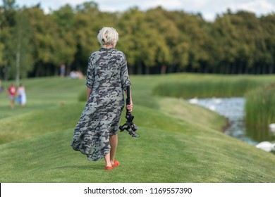 Blond woman walking alongside a lake carrying a tripod and camera as the wind blows the fabric of her long dress to the side, rear view