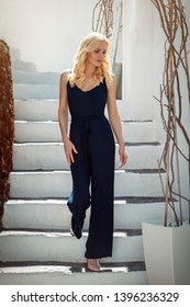 blond woman walking up and down stairs, in a blue jump suit, in Oia on Santorini