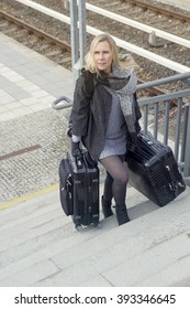 blond woman walking up stairs with heavy suitcases at train station