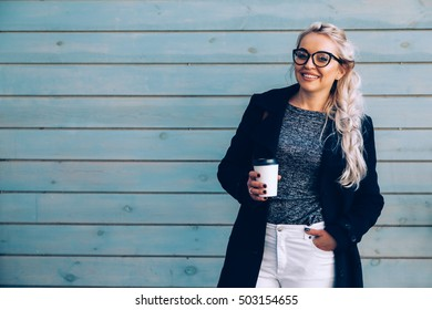Blond woman wearing black coat, white pants, hipster glasses drinking take away coffee in paper cup standing against cafe wall on city street. Casual fashion, elegant everyday look. Plus size model.