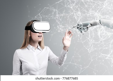 Blond woman wearing VR glasses is touching a robot hand. A gray wall background with polygons. Double exposure