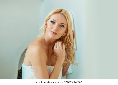 blond woman in a white bathroom looking at her reflection in the mirror, wearing a towel