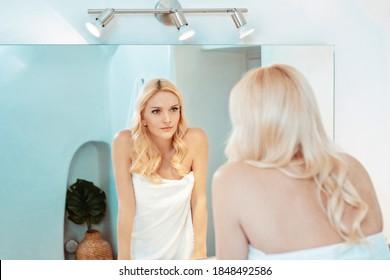 blonde Frau in einem weißen Badezimmer, die ihr Spiegelbild anschaut und ein Handtuch trägt
