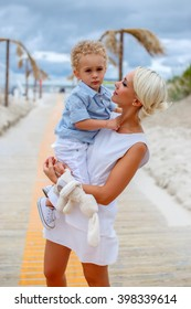 Blond woman in a white dress holds little boy in a blue shirt.