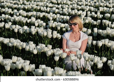 Blond woman in white flowers. Tulip Festival. Abbotsford. British Columbia. Canada.