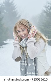 Blond woman in white snow winter with cross-country stick and knitwear
