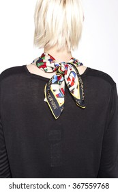 A blond woman(female, girl) wearing colorful scarf and black shirts back side isolated white at the studio.