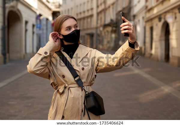 Blond Young attractive female traveler makes selfie, wears protective medical mask to protect herself from coronavirus. Travel Pandemic concept