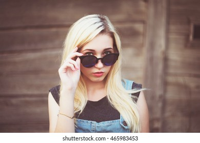 blond young caucasian teenage girl looking above sunglasses