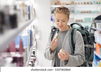 Blond young female traveler wearing coat and travel backpack choosing perfume in airport duty free store. Casual lady testing and buying cosmetics on the go in a beauty store.