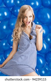 blond young happy girl in summer dress with hat taking pose with a lot of blue balloon in background. She looks in to the lens with open mouth, her right hand is on the hip and the left hand is near