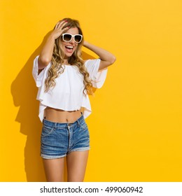 Blond young woman in jeans shorts, white shirt and white sunglasses holding head in hands, shouting and looking away, Three quarter length studio shot on yellow background.
