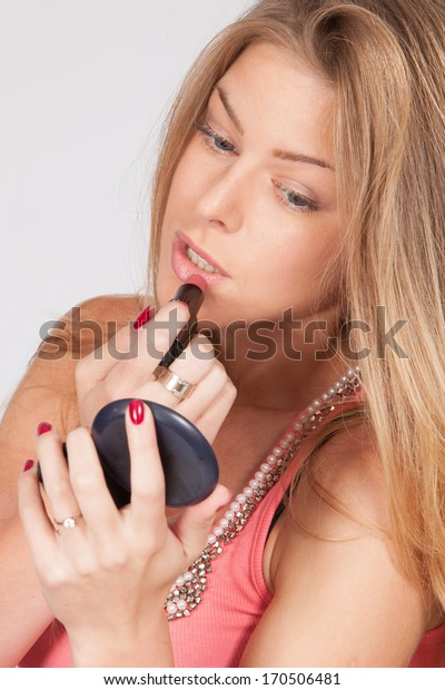 blond young woman put lipstick