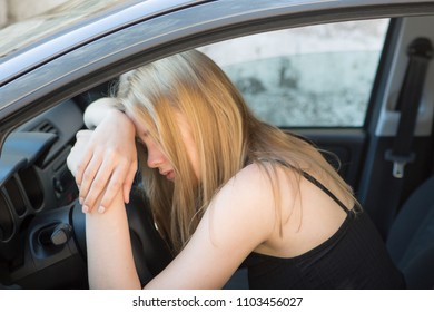 Blond young woman sleeping in a car