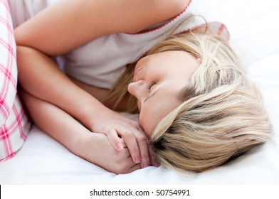 Blond young woman sleeping on a bed at home