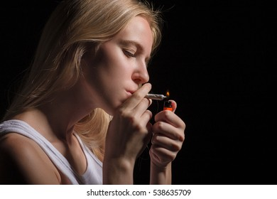 blond young woman smoking on black background