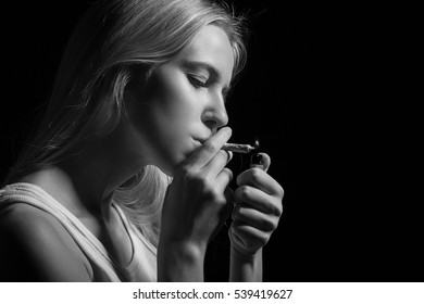 blond young woman smoking on black background, monochrome