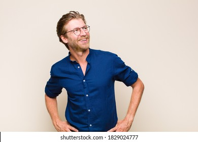 blonde adult caucasic man looking happy, cheerful and confident, smiling proudly and looking to side with both hands on hips