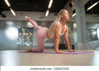 Blonde athlete standing on all fours on mat doing yoga.