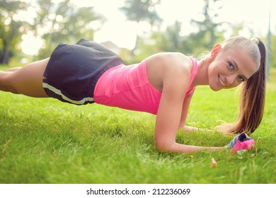 blonde athletic girl stretching and making exercises on grass in park