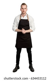 Blonde attractive chef wearing a white shirt and black apron standing with his hands clasped against a white background looking at camera.